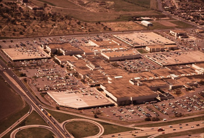 Aerial view of a large shopping mall with parking lots all around it. To the left and bottom of the image are highways.