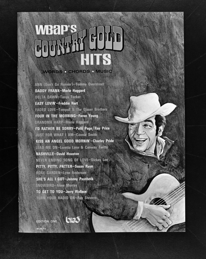 Black and white photograph of Country Gold Hits record book, with list of songs and artists. An illustration of a man with guitar and cowboy hat is in the lower right corner.