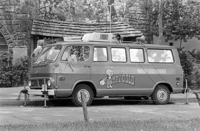 Black and white photo of a long van with a bullhorn and antenna on top. On the side is an illustration of a person holding a pick and a gold mining pan, with the words Country Gold.