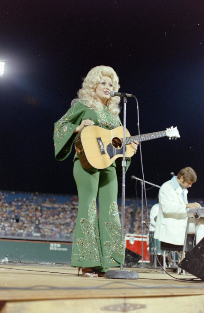 Photograph of Dolly Parton on stage holding an acoustic guitar and wearing a green bedazzled jumpsuit.