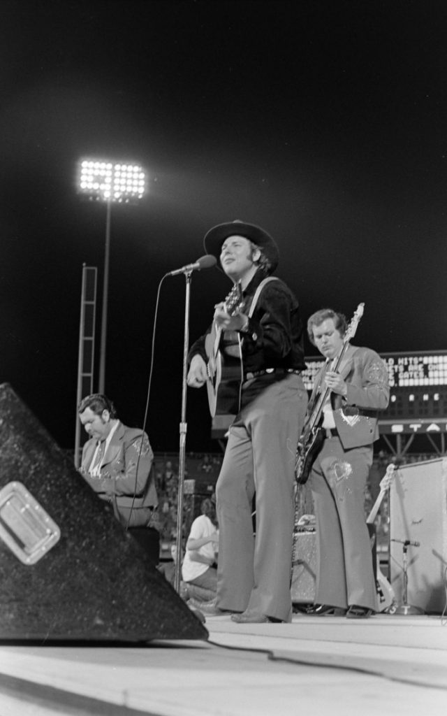 Black and white photo of Hank Williams Jr. performing on stage. He holds a guitar and wears a cowboy hat. Other musicians are behind him.