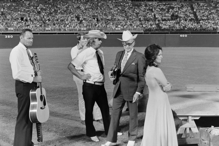 Black and white photo of Bill Monroe and the Blue Grass Boys standing on a field in a stadium. Two men stand with guitars.