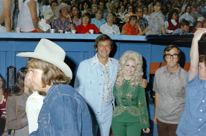 Photograph of Don Thomson with his arm around Dolly Parton's shoulders. He wears a light blue leisure suit, and she wears a green and bedazzled jumpsuit. Other people surround them.